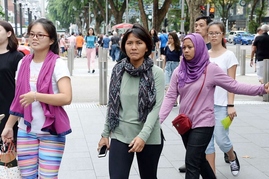 Singaporeans wearing warm clothing due to cold weather with average temperature between 23 and 25 degree celsius.
