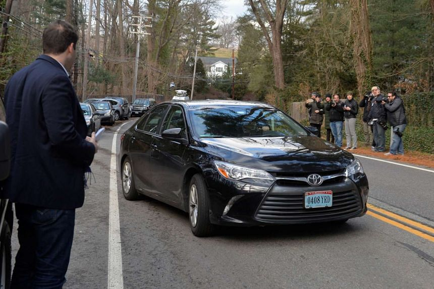 A vehicle with diplomatic licence plates passes journalists after departing from a Russian compound in Upper Brookville, Long Island, New York, Dec 30, 2016.