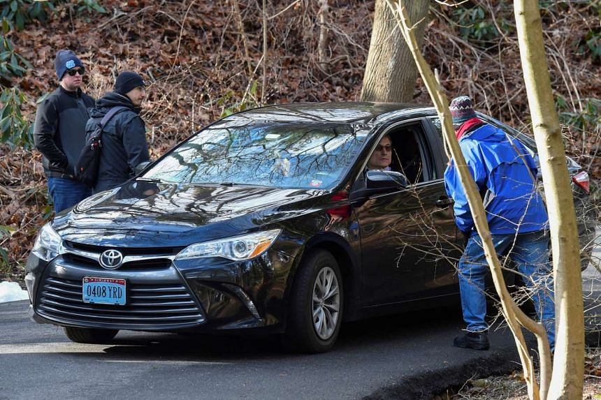 Unidentified security officials speak to a man in a vehicle with diplomatic licence plate outside the gates of a Russian compound in Upper Brookville, Long Island, New York, on Dec 30, 2016.