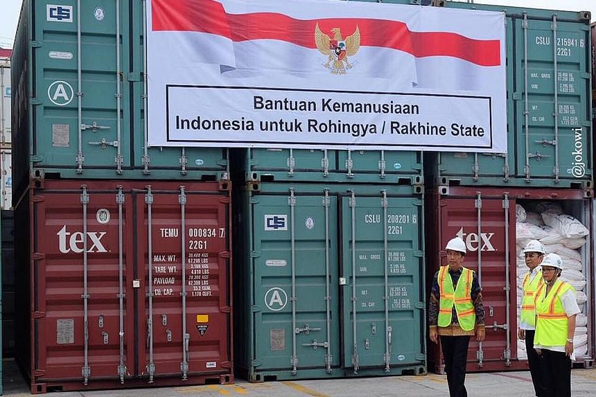 Indonesian President Joko Widodo (in batik shirt) inspecting an aid consignment destined for Myanmar's Rakhine state at the Tanjung Priok Port on Thursday. Ten freight containers filled with instant noodles, baby food, wheat, cereals and sarongs were