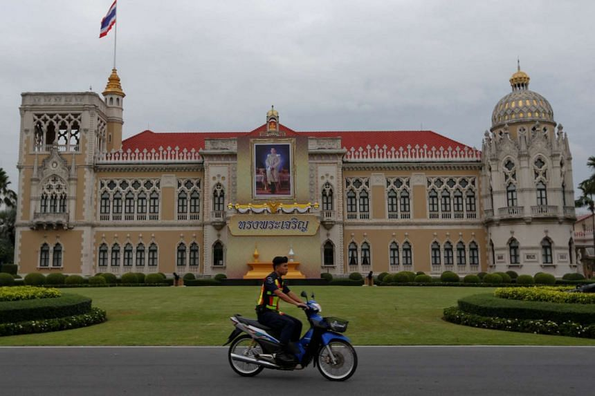 A police officer rides his motorcycle past a picture of Thailand's King Maha Vajiralongkorn Bodindradebayavarangkun installed at the Government House in Bangkok on Dec 6, 2016.