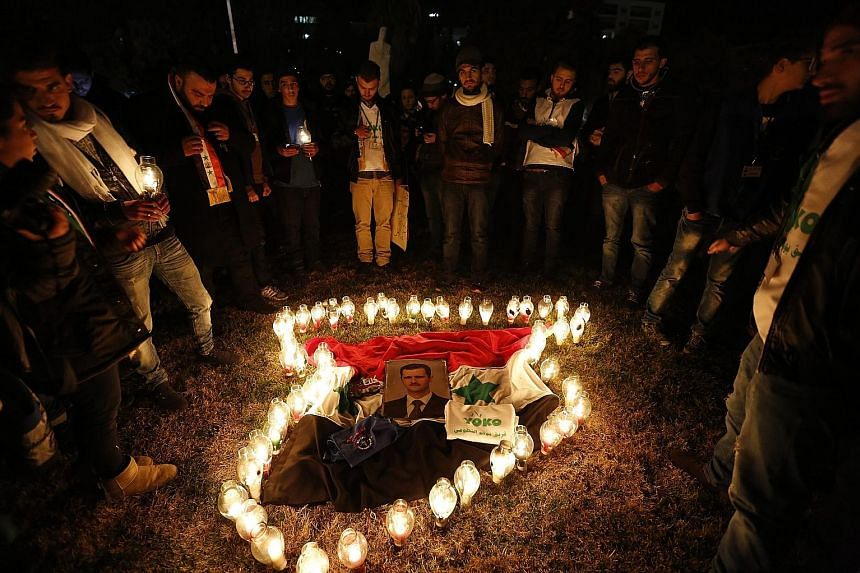 Candles arranged in the shape of the Syrian map surround a picture of President Bashar al-Assad during a vigil for peace at the Umayyad Square in Damascus. The vigil was held last Friday. A nationwide truce has been threatened by continued fighting i