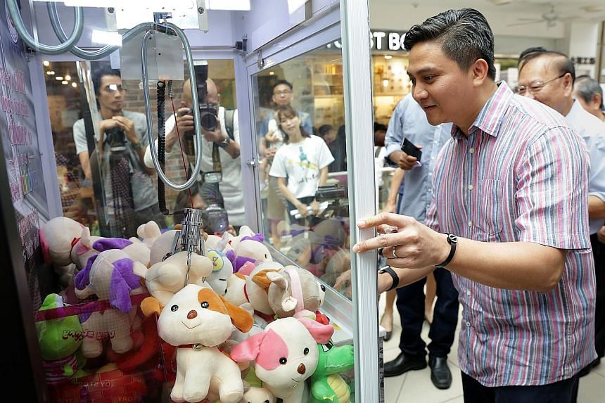 Bishan-Toa Payoh GRC MP Saktiandi Supaat trying out the claw machine yesterday. Money raised from users trying their luck at getting a stuffed toy from the machine will go towards THK's services.