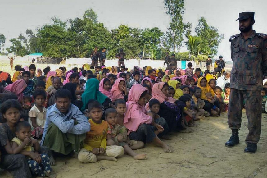 Rohingya Muslims from Myanmar, who tried to cross the Naf river into Bangladesh to escape sectarian violence, are kept under watch by Bangladeshi security officials in Teknaf on Dec 25, 2016.