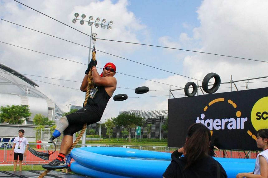 Full-time athlete Shariff Abdullah, also known as Singapore's Blade Runner, on the Final Obstacle, which featured a zip-line ending over a pool of water, during the 14km obstacle race of the seventh edition of the Men's Health Urbanathlon on Marc