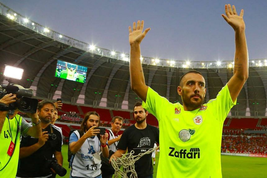 Brazilian player Alan Ruschel (R) of Chapecoense, who survived the team's plane accident in Colombia, salutes prior to the 'Lance de Craque' charity game, held to honor the victims of the Chapecoense plane crash tragedy, at Beira Rio stadium in Porto