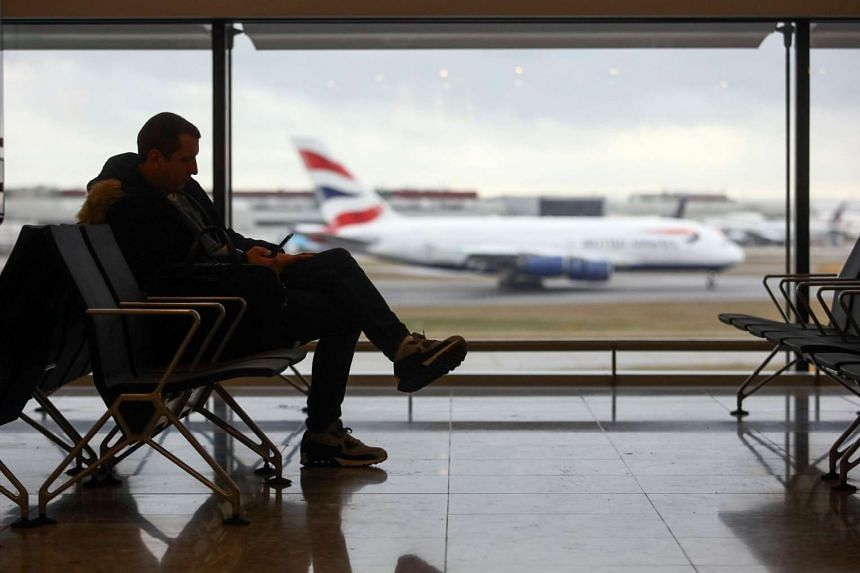 A passenger sits at a departure gate against a backdrop of a British Airways aircraft landing, at terminal 2 at London Heathrow Airport in London, UK on Dec 23, 2016.