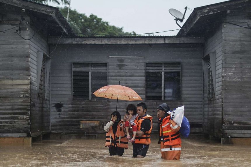 A Malaysia Civil Defence Force officer (right) accompanies a family as they wade through the flood during rain at Machang, Kelantan, Malaysia on Jan 3, 2016.