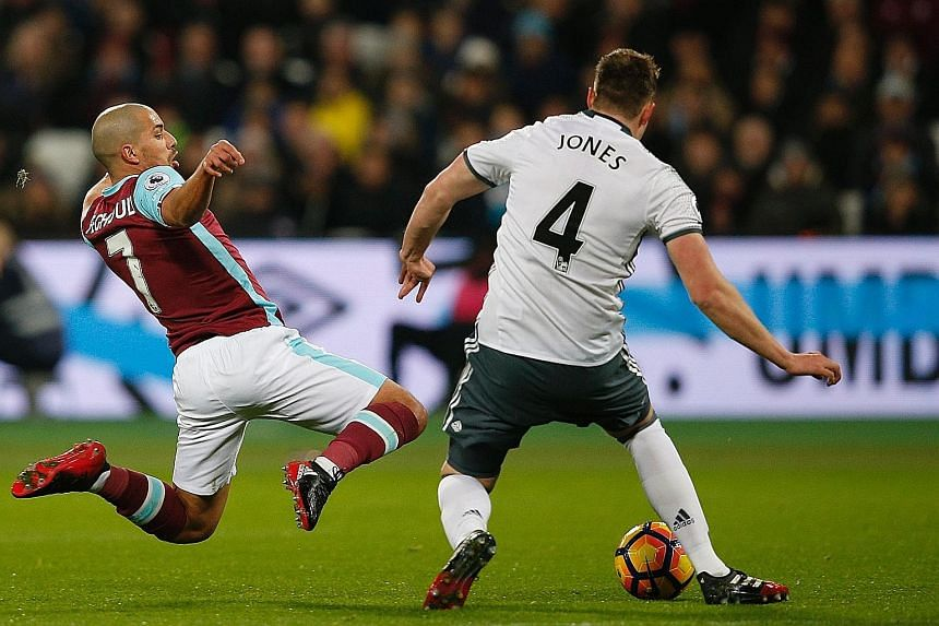 West Ham midfielder Sofiane Feghouli leaping in to challenge United defender Phil Jones. The Algerian is sent off for the tackle after he catches his opponent on the follow- through.