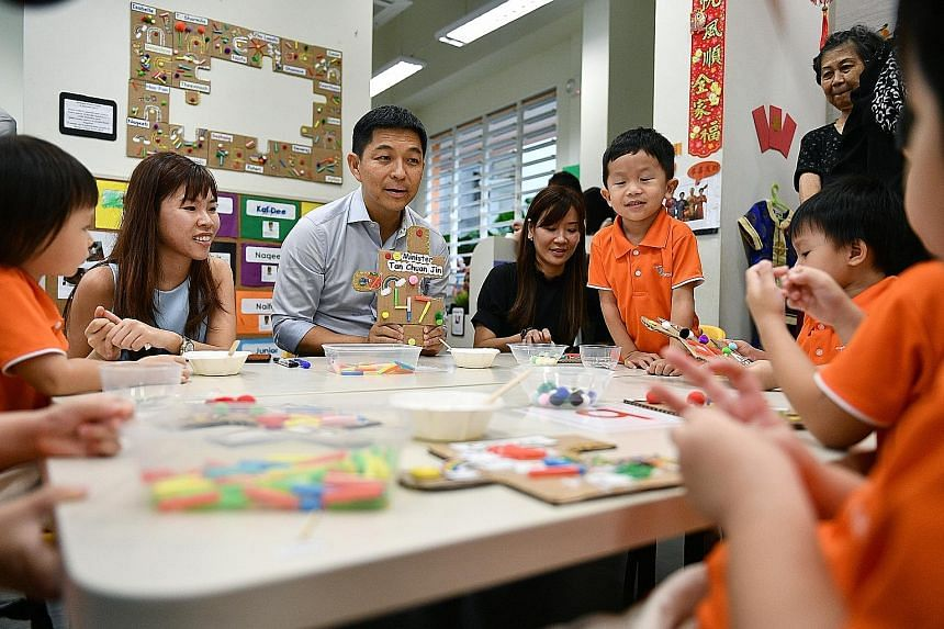 Minister for Social and Family Development Tan Chuan-Jin interacting with pre-schoolers at Mr First Skool in Boon Lay Drive yesterday. With him are Ms Nicole Kin (left) and Ms Celia Teo, principal of the pre-school.