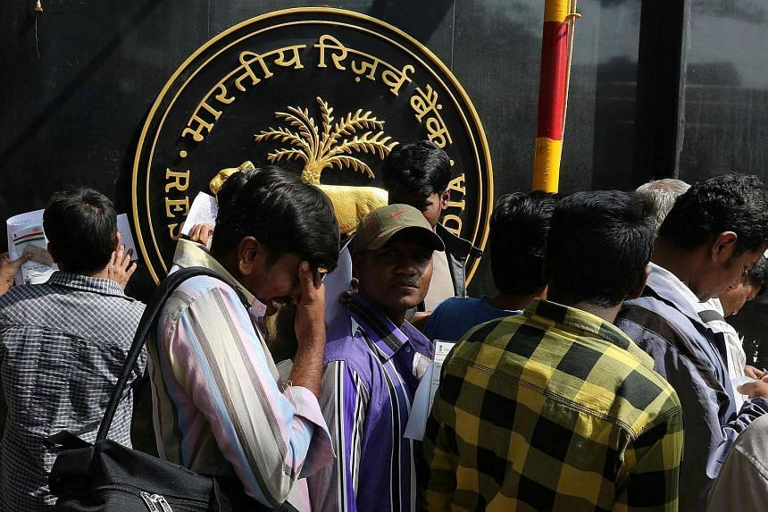 Indian people line up outside the Reserve Bank of India (RBI) to deposit old Indian rupee notes, in Bangalore, India on Dec 30, 2016.