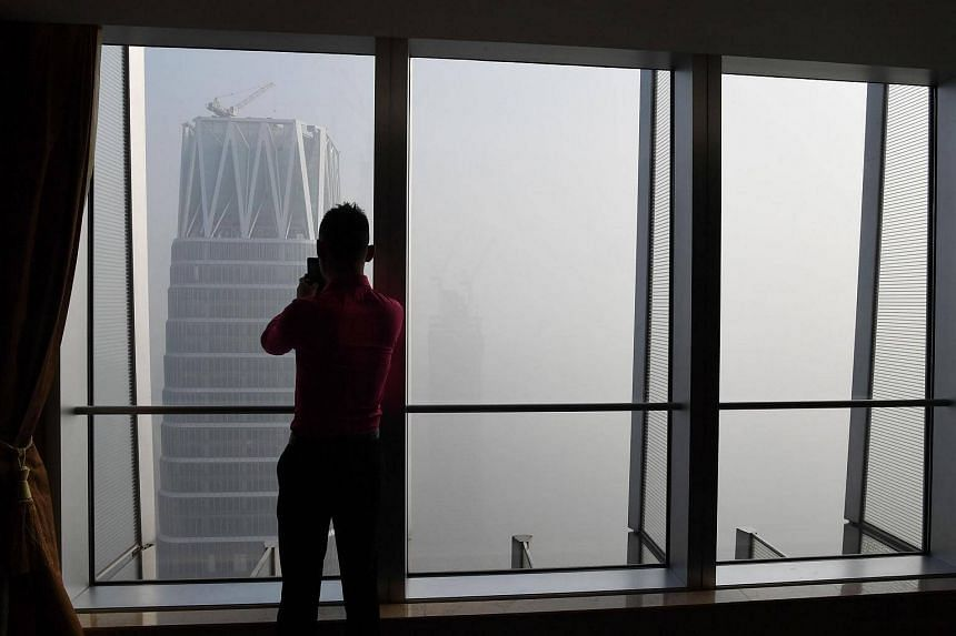 A man taking photos of buildings on a polluted day in Beijing, on Jan 1, 2017.