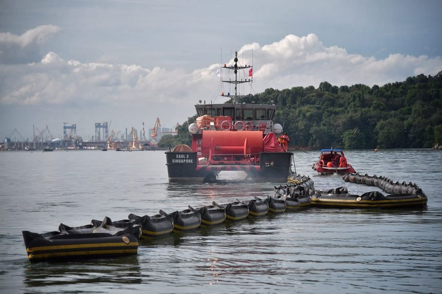 A boat from Oil Spill Response using an oil boom in waters off the western portion of Pulau Ubin, on Jan 4, 2017.