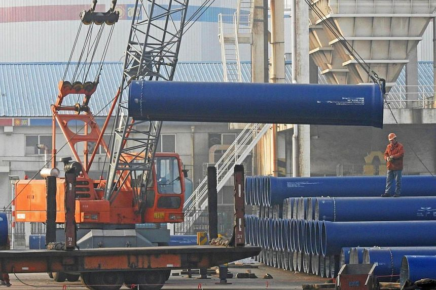 Chinese workers loading steel pipes at a port in Lianyungang, east China's Jiangsu province, on Jan 1, 2017.
