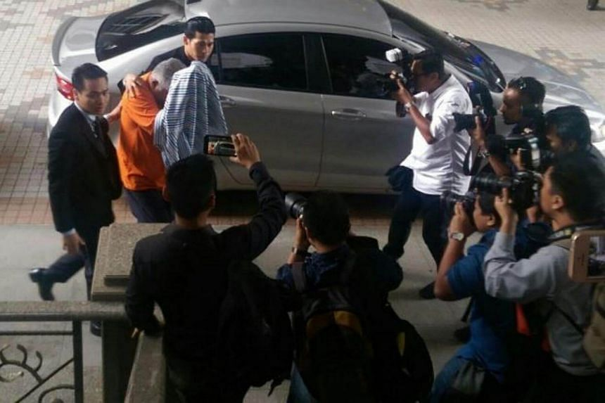 One of the suspects believed to be Rural and Regional Development Ministry secretary-general Mohd Arif Ab Rahman (in orange lockup uniform) arriving at the court house in Putrajaya.