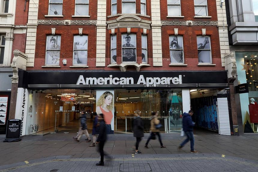 Shoppers pass a closed down American Apparel LLC fashion retail store on Oxford Street during the Boxing Day sales in London on Dec 26, 2016.