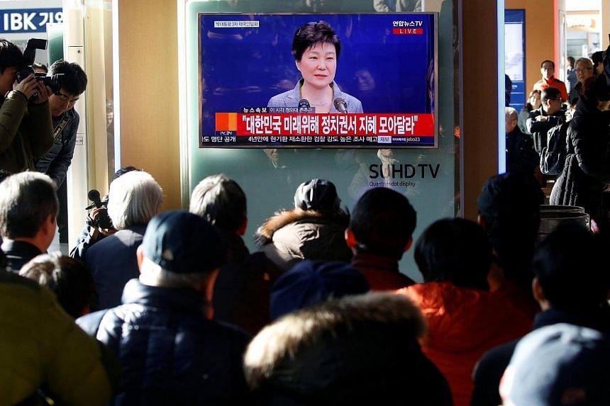 People watch a television broadcast of a news report on President Park Geun Hye releasing a statement to the public in Seoul, South Korea.