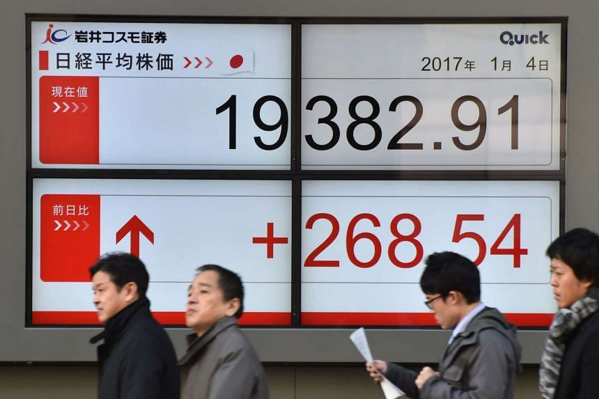 Pedestrians walk past an electric quotation board flashing the Nikkei key index of the Tokyo Stock Exchange in front of a securities firm in Tokyo on Jan 4, 2017.
