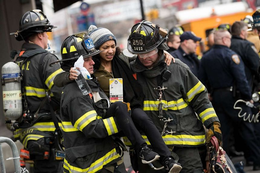 Fire-fighters carry an injured person away at the scene of a train derailment in Brooklyn, New York, Jan 4, 2017.