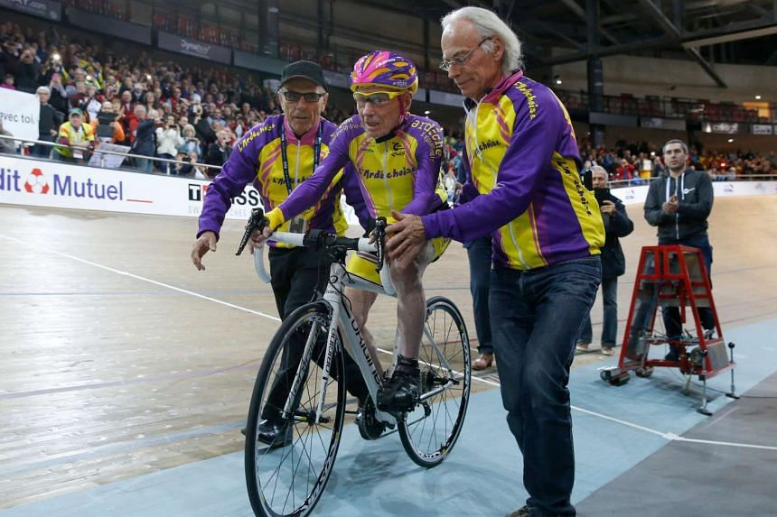 Marchand (centre) on his bike as he attempts to break his own world cycling record at the age of 105.