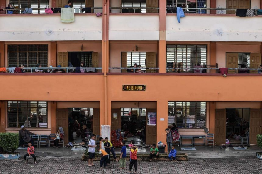 Residents displaced from floods gather in a school used as a relief centre in Malaysia's north-eastern town of Rantau Panjang on Jan 5, 2017.