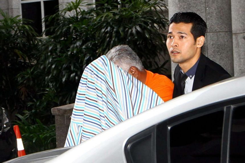 A Malaysian Anti-Corruption Commission officer escorts Datuk Mohd Arif Ab Rahman after a remand order was granted on his corruption case at the Magistrates Court in Putrajaya.
