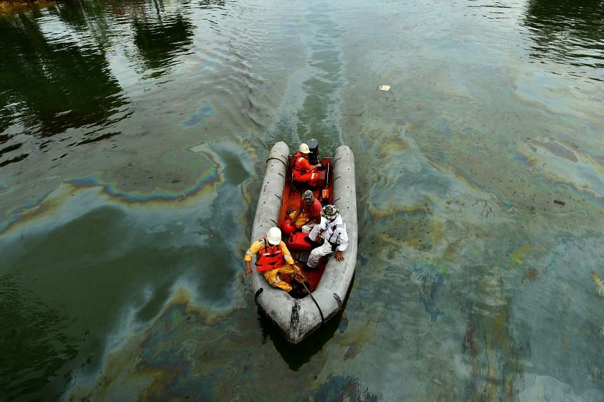 A boat carrying personnel from the Singapore oil spill response centre travelling in water stained with oil near Changi jetty on Jan 5, 2017.