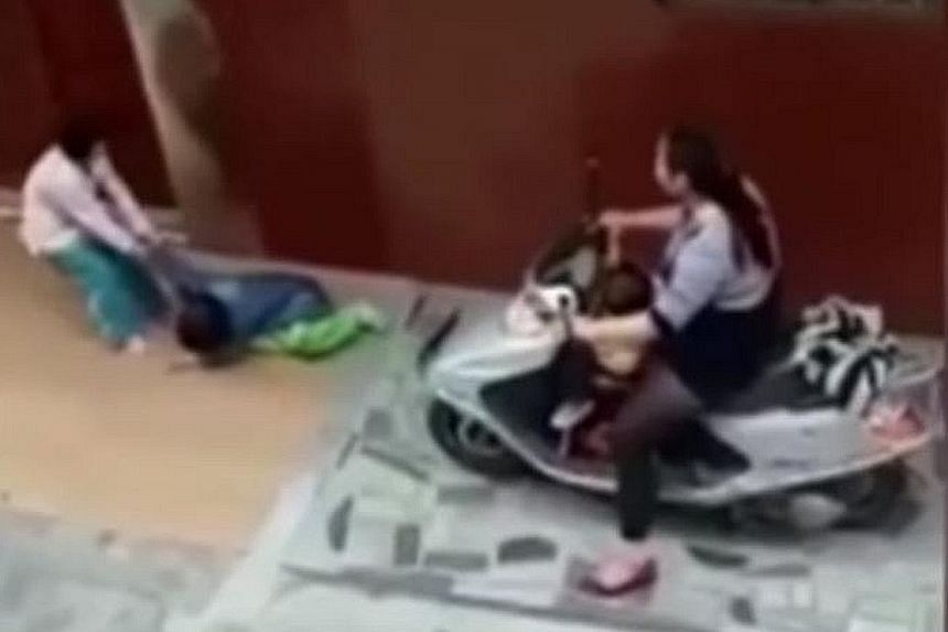 A video shot by an eyewitness shows the woman's child dragging the injured girl, before the woman rides her scooter over her again.