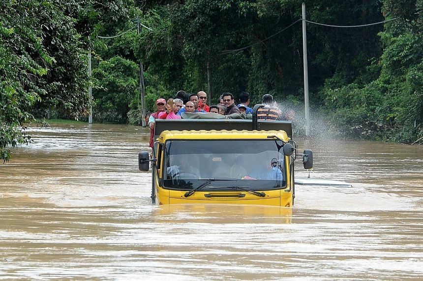 Flood victims using a lorry to travel in Kampung Bekuk in the north-eastern Malaysian state of Terengganu after a road was closed to light vehicles yesterday. The number of evacuees rose sharply to 12,910 from 4,352 the previous day after heavy rain