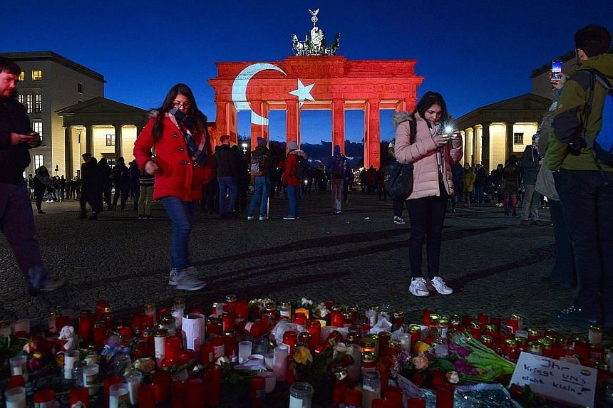 A makeshift memorial to victims of the Istanbul nightclub attack was set up near Berlin's Brandenburg Gate, which was illuminated in the colours of the Turkish flag on Monday. The monument was one of the sites allegedly targeted by ISIS for an attack