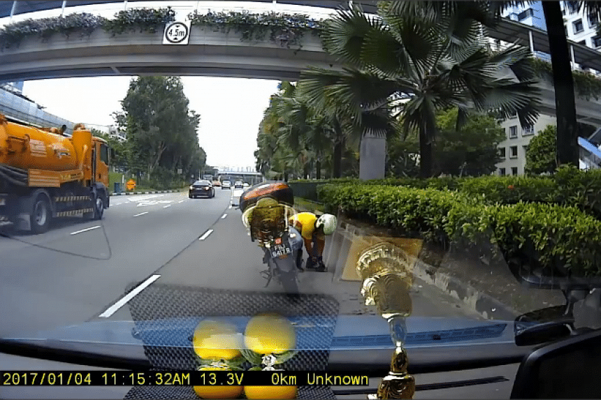 A motorcyclist riding on the right-most lane of Woodlands Avenue 7, stopped his vehicle to save a bird on the road.