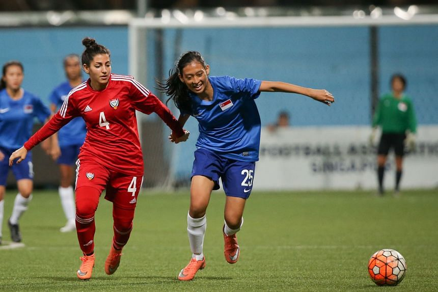 Singapore's national women's footballer Faradila Rafidi (No. 25) tussling for the ball with her United Arab Emirates counterpart Alanood Aladwan during a friendly at Jalan Besar Stadium last night. The visitors won 4-0 through goals from Naeema Ghari