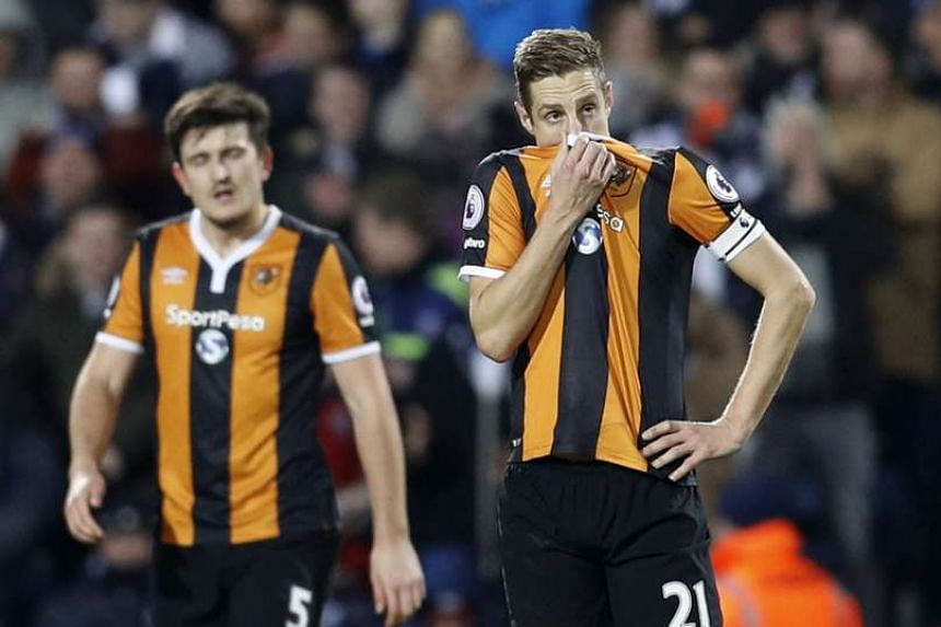 Hull City's Michael Dawson (right) looking dejected after their 1-3 loss to West Bromwich Albion on Monday. The result triggered the departure of manager Mike Phelan.