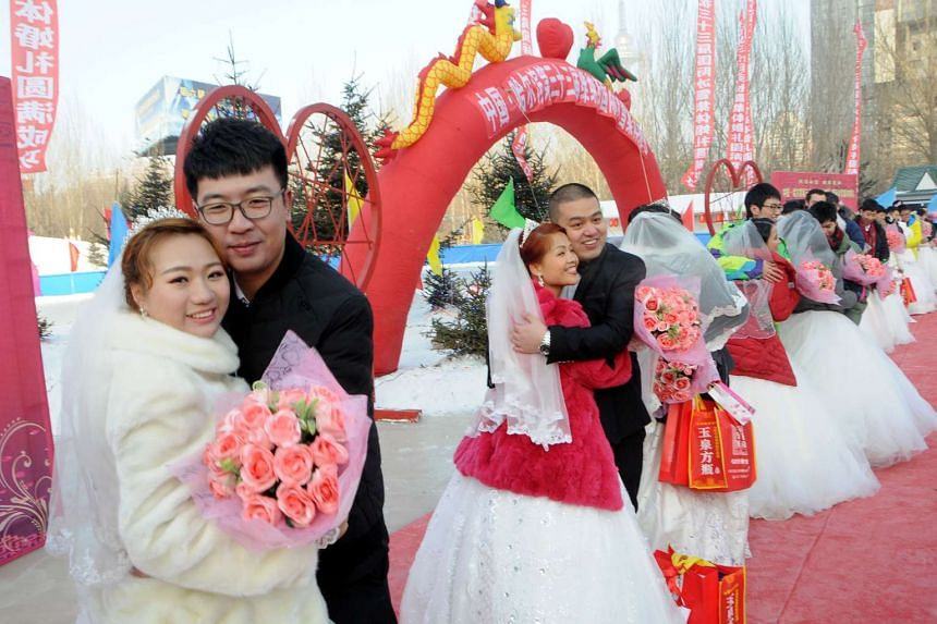 Couples attend a mass wedding on the second day of Harbin's International Ice Festival, in Harbin on Jan 6, 2017.