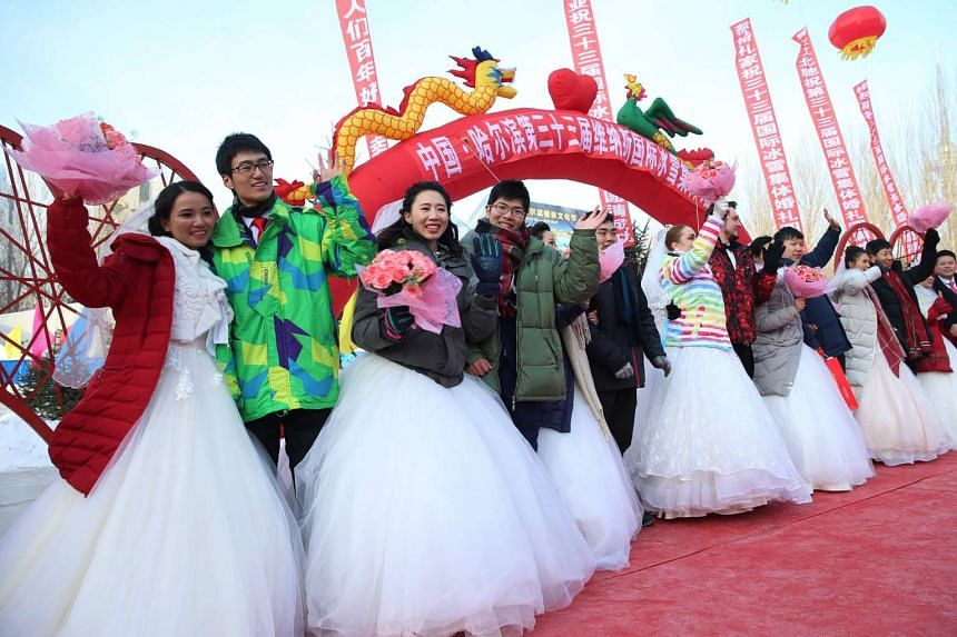 Couples attend a mass wedding ceremony on the second day of Harbin's International Ice Festival, in Harbin on Jan 6, 2017.