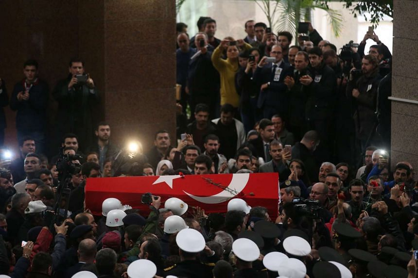 A coffin is carried during the funeral ceremony of Turkish police officer Fethi Sekin and courthouse officer Musa Can at the courthouse of Izmir on Jan 6, 2017.