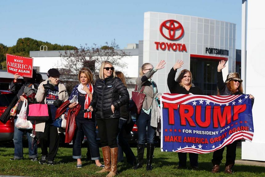 Supporters of Republican presidential candidate Donald Trump stand outside a Toyota car dealer before a campaign event on Oct 15, 2016 in Portsmouth, New Hampshire.