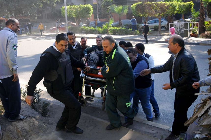 Egyptian emergency services carry a wounded victim at the site of a bomb attack next to a police checkpoint in the western Talibiya district of the capital Cairo on Dec 9, 2016.