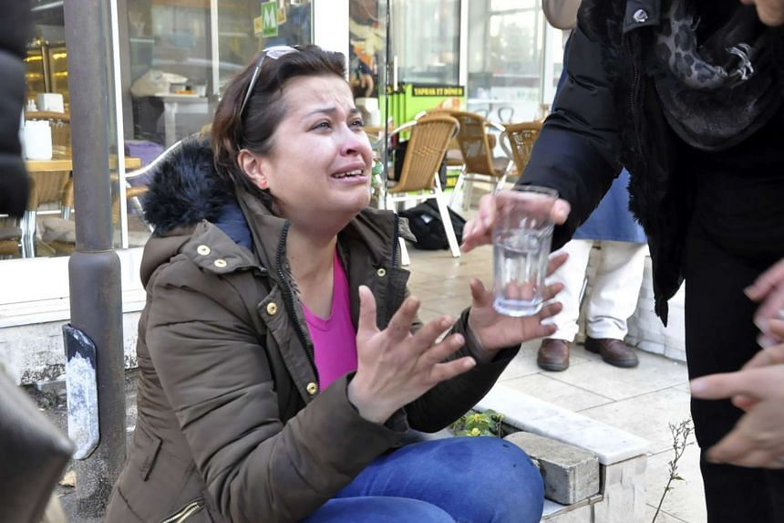 A woman reacts as she is given a glass of water near the scene of a car bomb outside the courthouse in Aegean coastal city of Izmir on Jan 5, 2017.