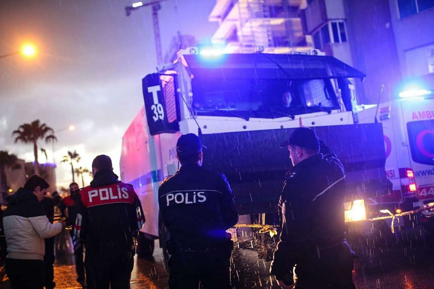 Turkish police officers stand guard at the site of an explosion in front of the courthouse in Izmir on Jan 5, 2017.
