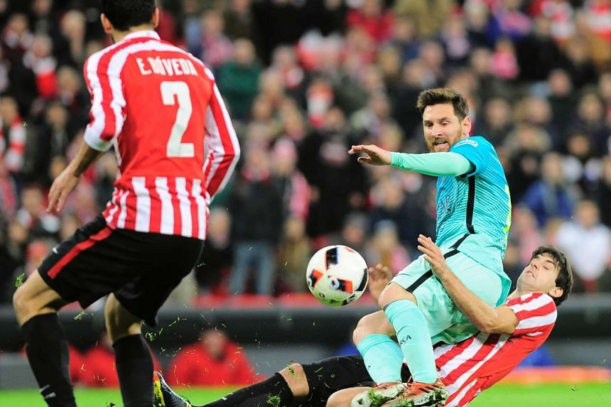 Barcelona's Lionel Messi (centre) vies with Athletic Bilbao's Mikel San Jose during the Spanish Copa del Rey (King's Cup) round of 16 first leg football match.