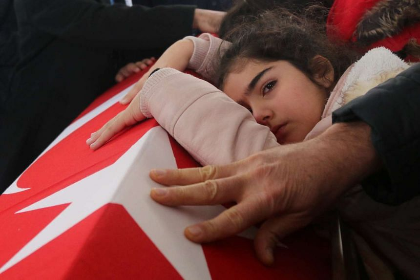 Nisa, eight-year old daughter of police officer Fethi Sekin, who was killed in the Izmir courthouse attack on Thursday, mourns over her father's coffin during a funeral ceremony in Izmir, Turkey, on Jan 6, 2017.