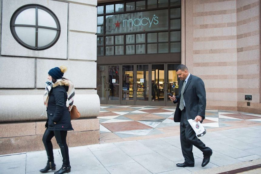 People walk past a Macy's department store in Washington DC on January 5, 2017.