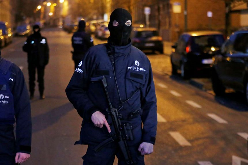 A Belgian police officer stands guard at the scene of a security operation in the Brussels district of Molenbeek, Belgium, on March 18, 2016.