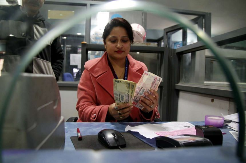 An Indian bank clerk counts old high denomination Indian rupee notes after receiving them from a customer at a bank in Jammu, India on Dec 30, 2016.