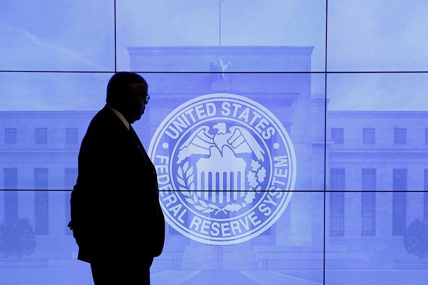 A security guard walks in front of an image of the Federal Reserve in Washington, DC, US.