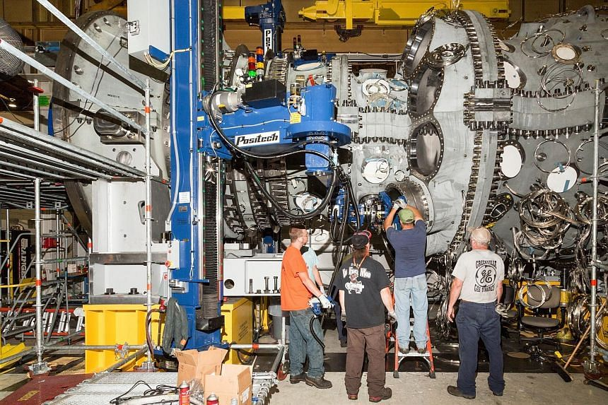 Workers use a robotic arm to install components of a gas turbine at GE's factory in Greenville, South Carolina. The recovering manufacturing sector is expected to give a shot in the arm to the world economy this year, but growth is still likely to be