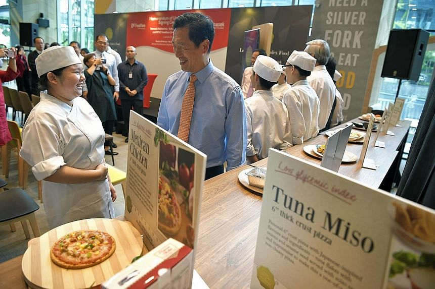 Minister for Education (Higher Education and Skills) Ong with Temasek Polytechnic student Than Jia Hui, 19, who is studying baking and culinary science, at the launch of the initiative between the polytechnic and NTUC Foodfare.