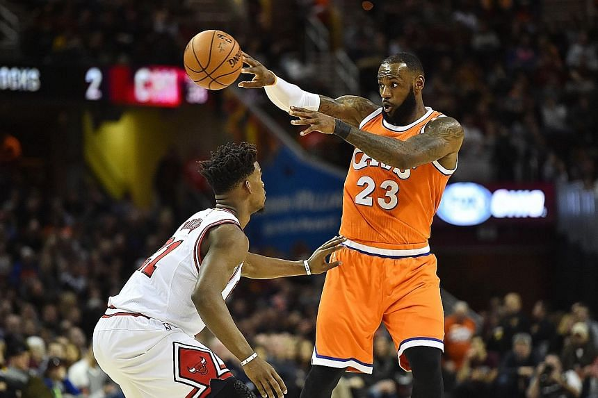 Cavaliers forward LeBron James passes as Bulls forward Jimmy Butler defends during the first half of their NBA clash at Quicken Loans Arena. James (31 points) and Butler (20) were their respective teams' top scorers.