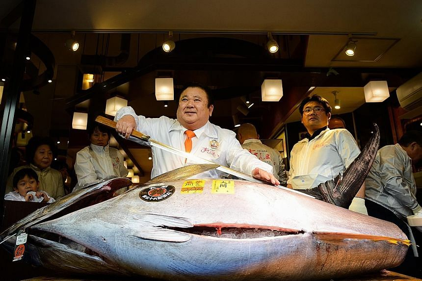 """Japan's self-styled """"Tuna King"""" Kiyoshi Kimura with his latest catch - a 212kg Pacific bluefin tuna that he paid 74.2 million yen (S$913,000) for at the first auction of the new year at Tokyo's Tsukiji fish market yesterday. Mr Kimura, president of"""